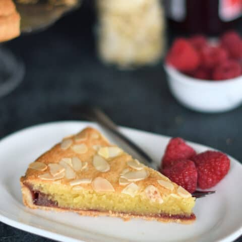 a slice of bakewell tart in a plate with a fork and raspberries