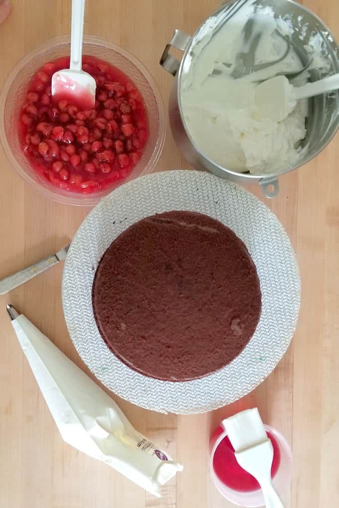 Cherries, whipped cream, kirschwasser syrup and chocolate cake assembled on a table.