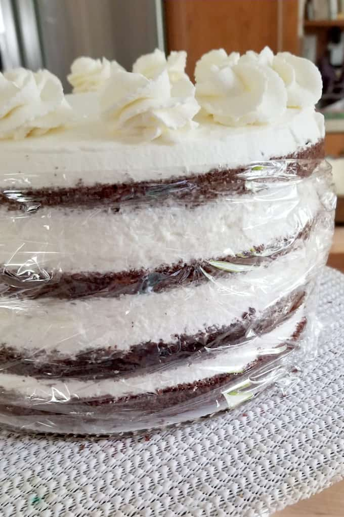 showing how to wrap the sides of a black forest cake with plastic to prevent it from drying out.