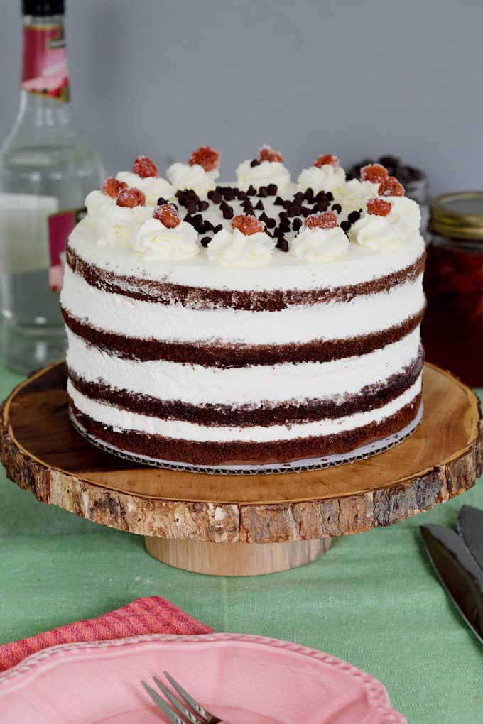 A black forest layer cake set on a wooden cake stand.