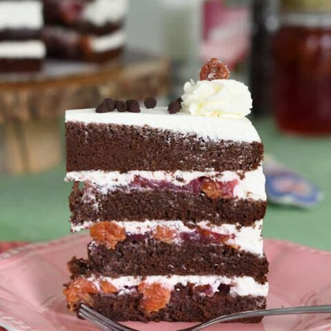 a slice of black forest cake on a pink plate