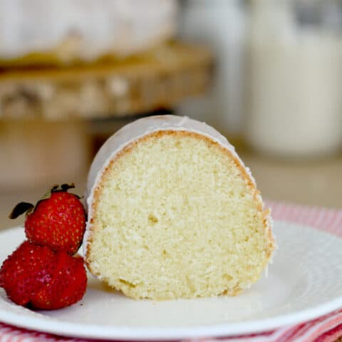 a slice of sourdough bundt cake on a plate with a few strawberries