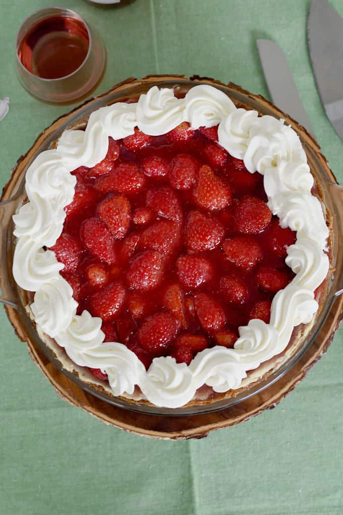 An overhead view of a fresh fresh strawberry pie with whipped cream border.