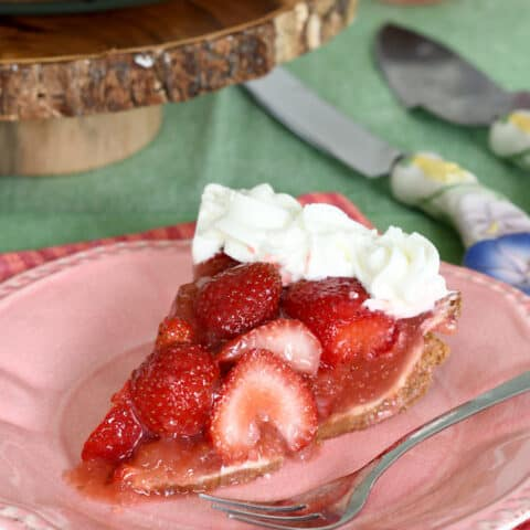 a slice of fresh strawberry pie on a pink plate