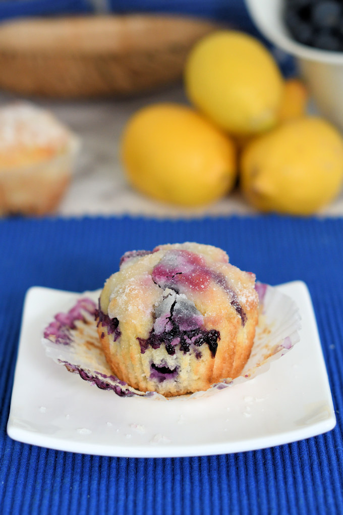 an unwrapped lemon blueberry muffin on a plate