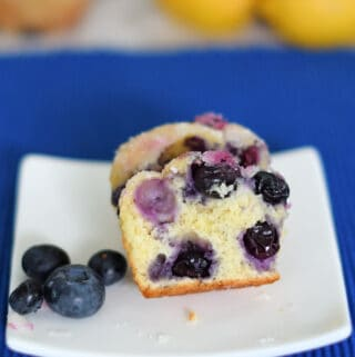 a lemon blueberry muffin cut in half on a plate