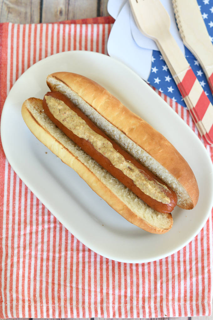 a hot dog with mustard on a homemade bun with red, white & blue table setting