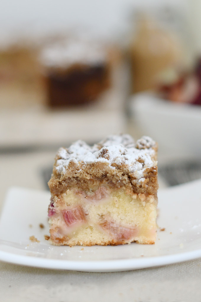 a piece of rhubarb crumb cake on a small white plate