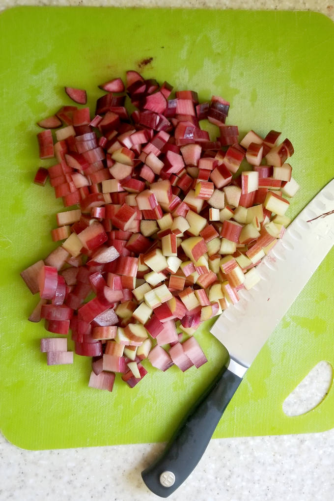 chopped rhubarb on a green cutting board with a knife