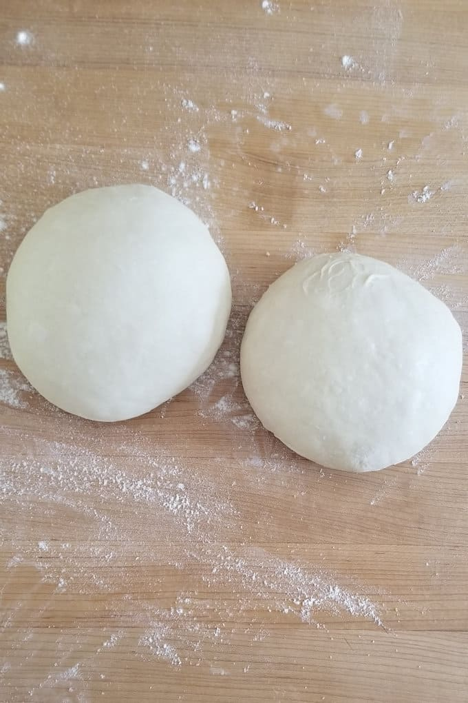 two balls of pizza dough on a butcher block surface