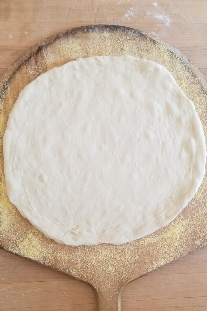 an unbaked pizza crust on a wooden peel dusted with cornmeal