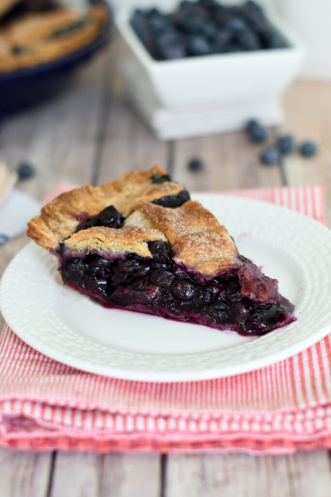 a slice of blueberry pie on a white plate
