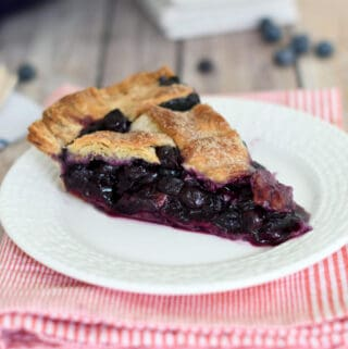 a slice of blueberry pie in a white plate