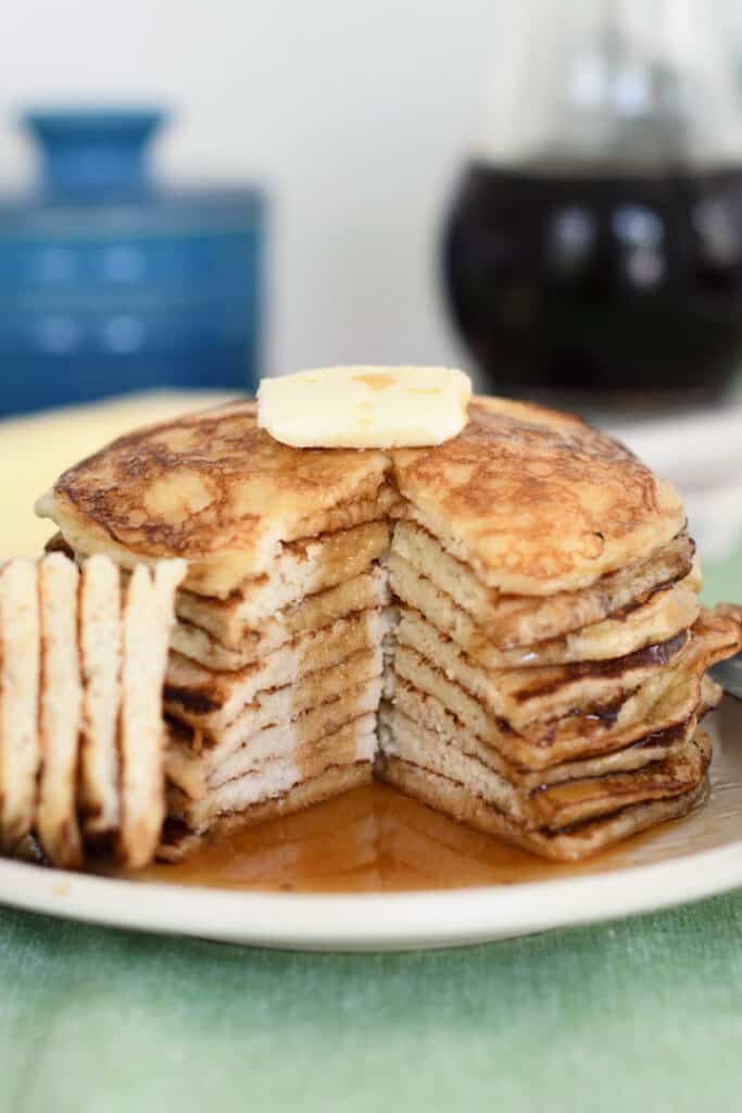 a stack of sourdough pancakes with a wedge cut out to show the middle of the pancakes. A pat of butter on top and syrup on the plate