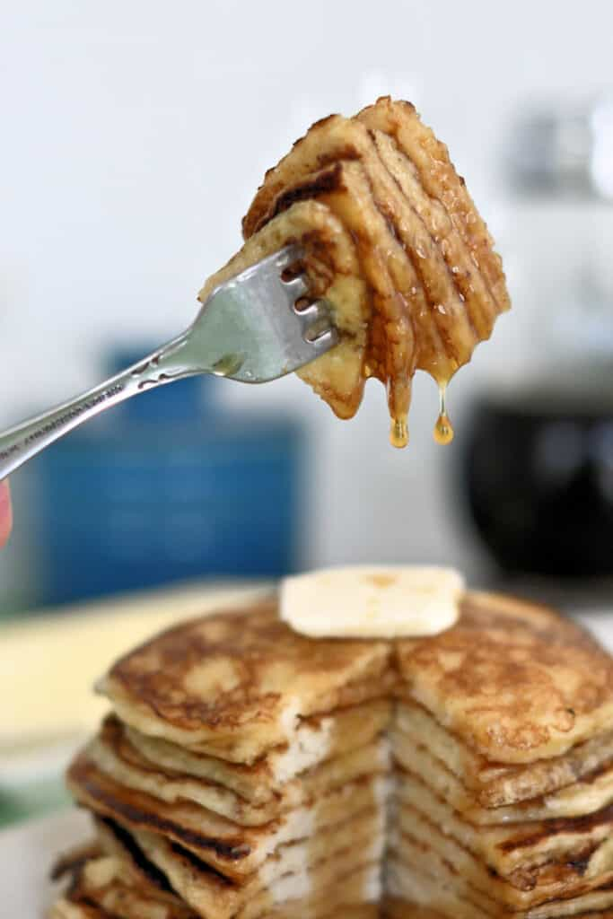 a forkful of sourdough pancakes with syrup dripping off