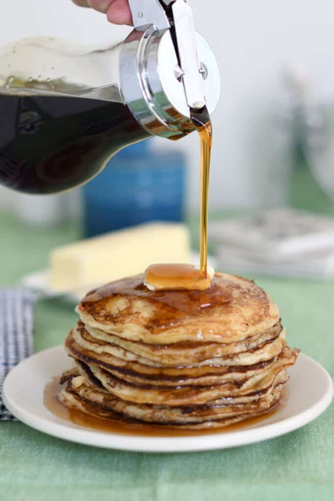 a stack of sourdough pancakes with syrup pouring over the stack