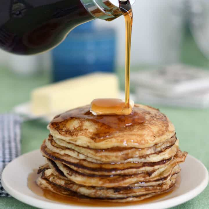 a stack of pancakes with syrup pouring over the stack