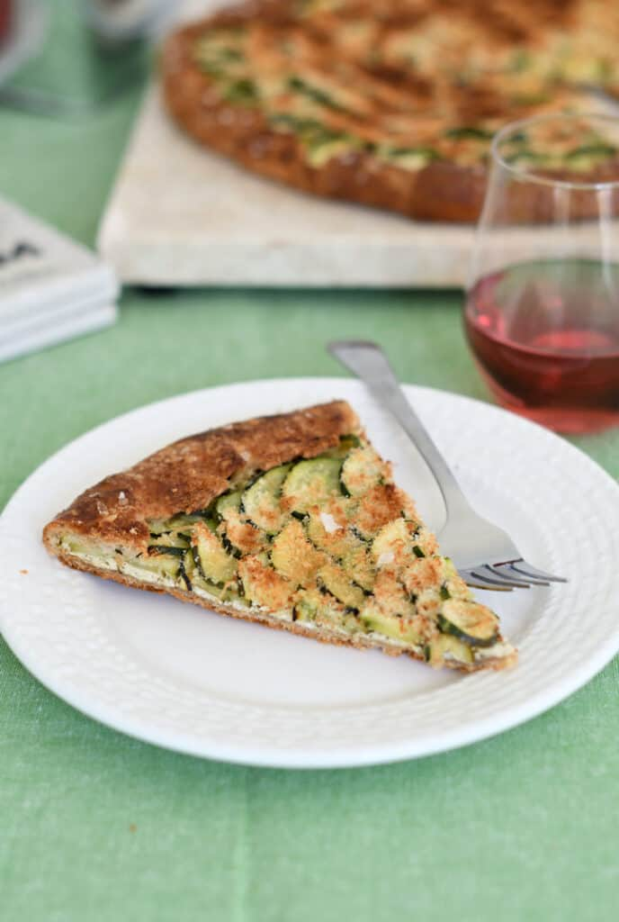 a slice of zucchini galette on a white plate with a glass of rose wine