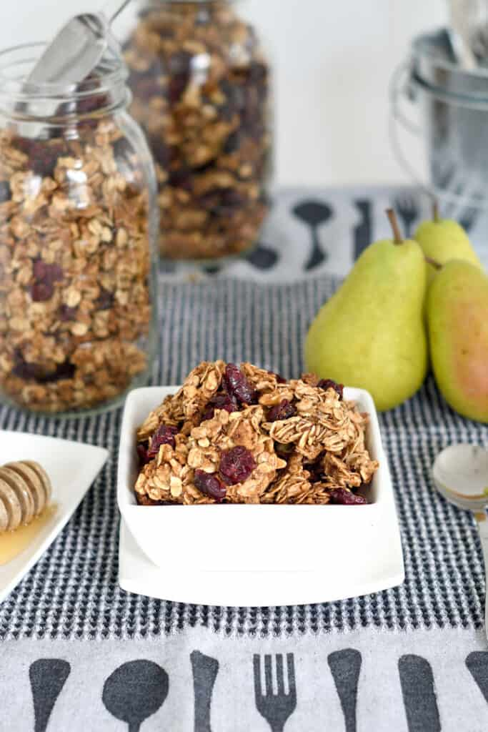 a bowl of chunky granola with a jar of granola in the background
