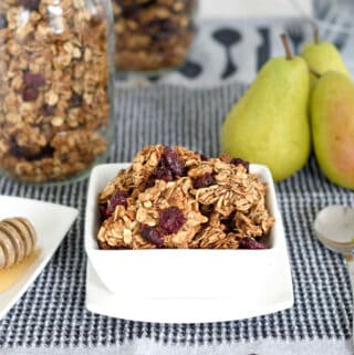an image of a bowl of chunky granola on a table with fruit and honey