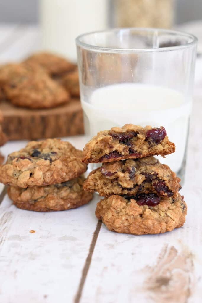 Two stacks of oatmeal cookies with cranberries and chocolate chips with a glass of milk.