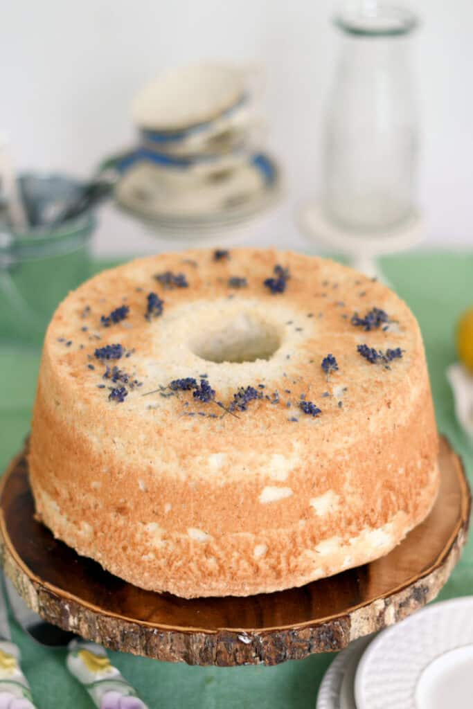 a lemon lavender angel food cake on a wooden cake stand. Lavender blossoms scattered on top of the cake