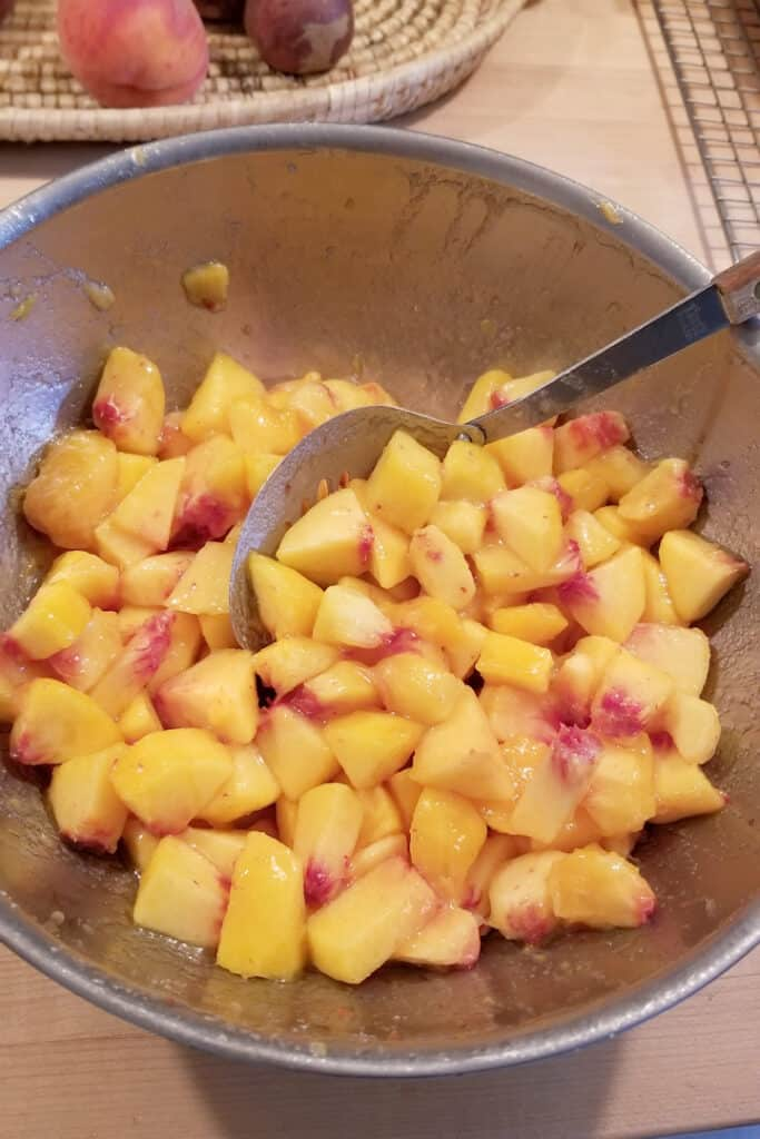 a bowl filled with chunks of fresh peaches macerating in sugar