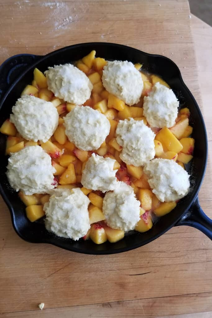 showing a peach cobbler with biscuit dough on top ready for the oven