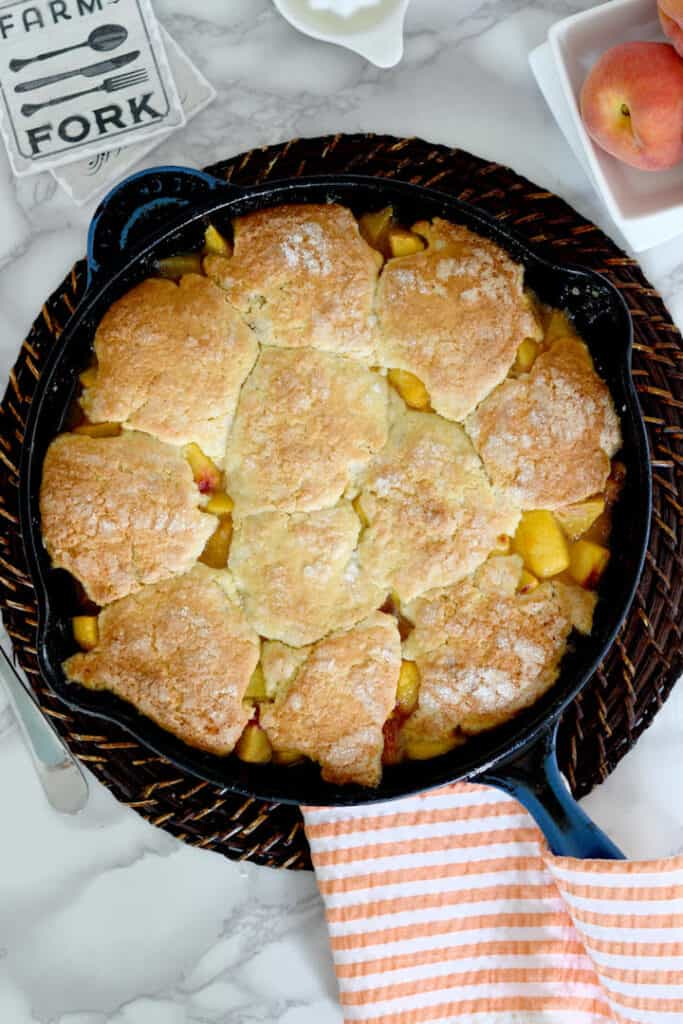 an overheat view of a cast iron skillet filled with fresh peach cobbler