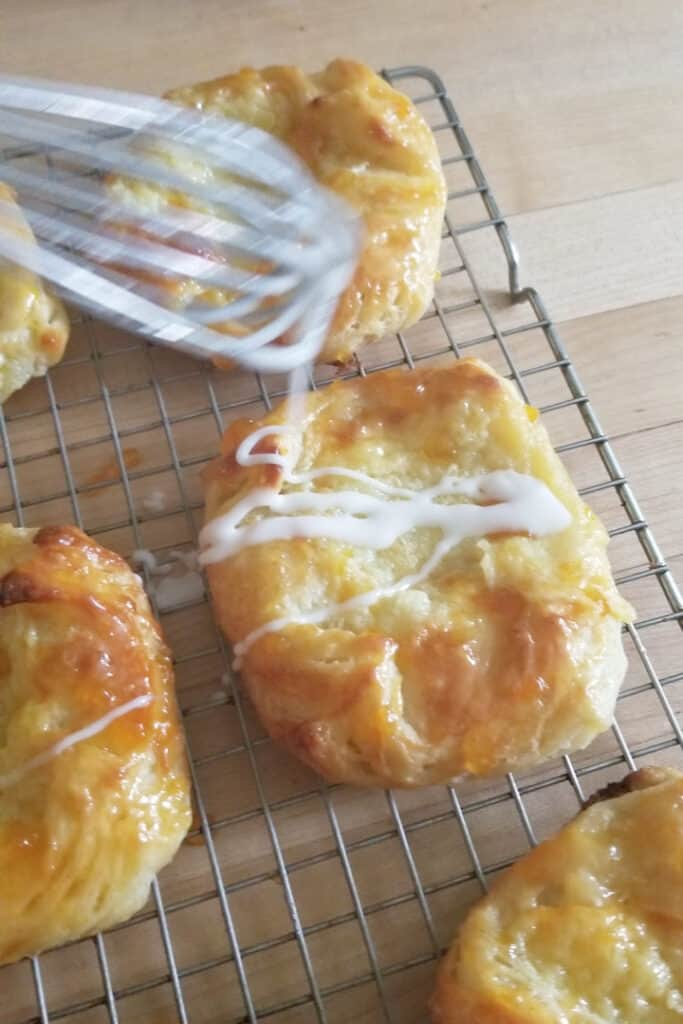 cheese danish on a cooling rack being glazed
