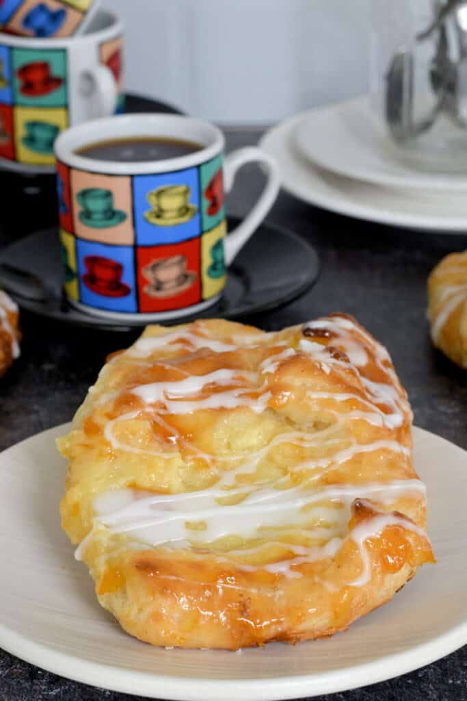 a glazed cheese danish on a plate