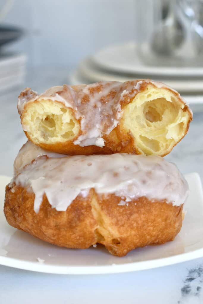 a french cruller on a plate with a broken cruller on top showing the open interior crumb
