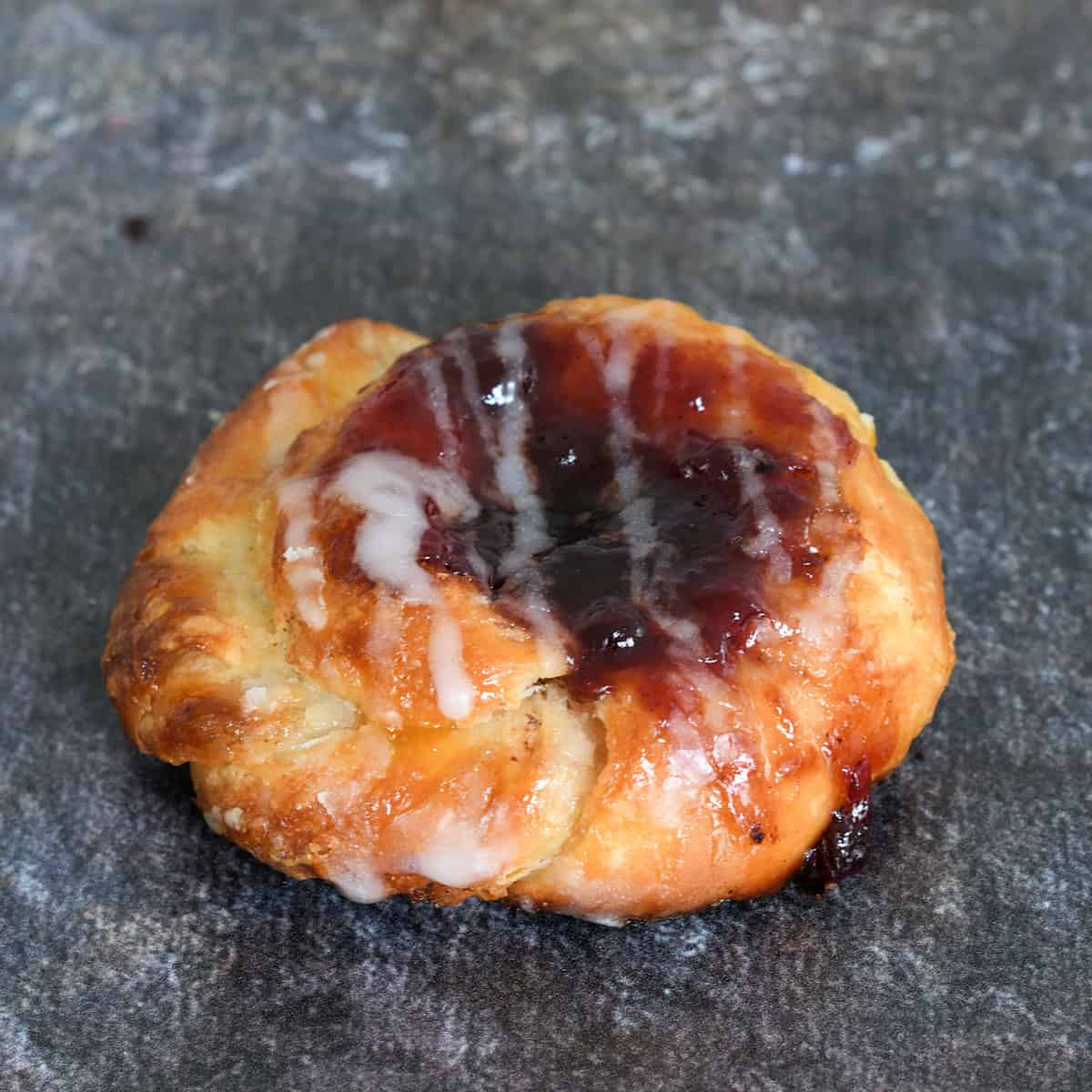 a sourdough danish pastry filled with jam is on a gray background