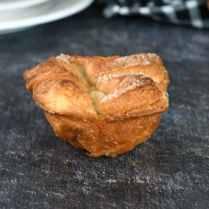 a kouign amann pastry on a black surface