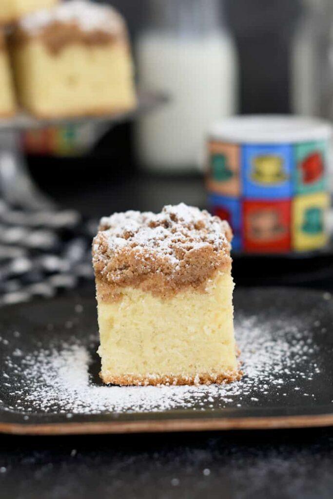 a slice of sourdough crumb cake on a black plate
