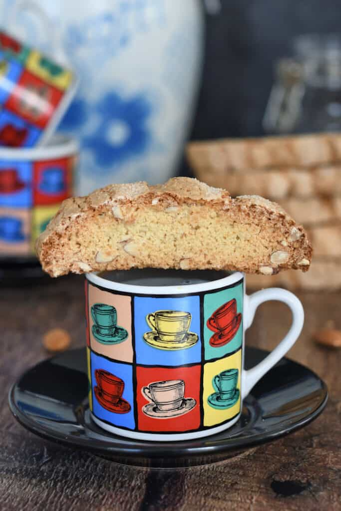 a sourdough biscotti cookie sitting on top of the cup of expresso