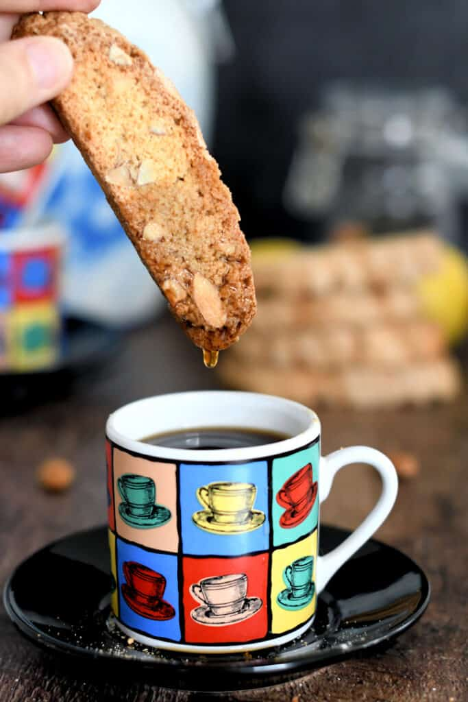 a biscotti being dunked in a cup of expresso