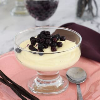 a dessert dish filled with vanilla mousse topped with wild blueberries