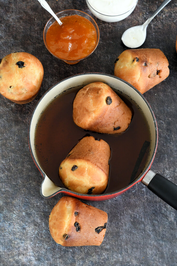 two baba pastries soaking in rum syrup.