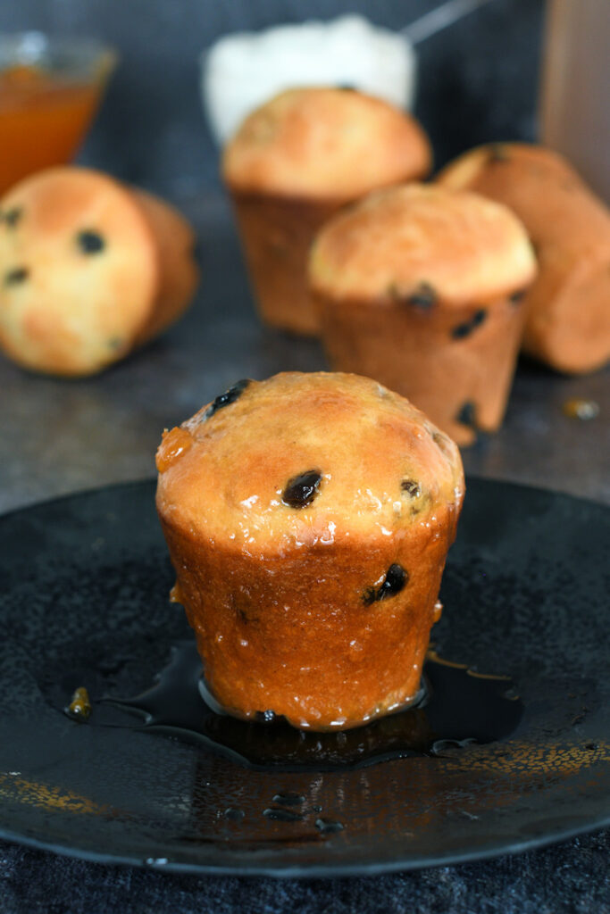 a sourdough baba au rhum on a plate in a pool of rum syrup