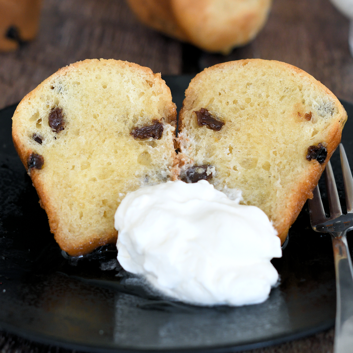 a baba au rhum on a plate with whipped cream