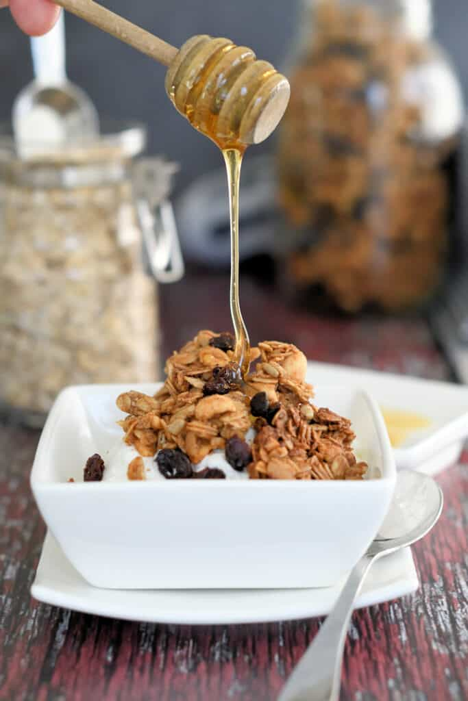 a bowl of yogurt topped with peanut butter granola with honey being drizzled on top