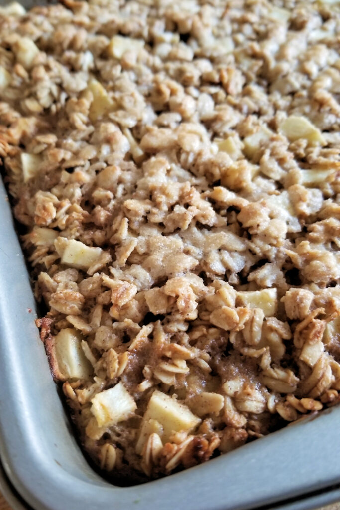 a closeup of apple maple baked oatmeal in a pan
