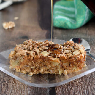 a slice of apple maple baked oatmeal on a plate being drizzled with maple syrup