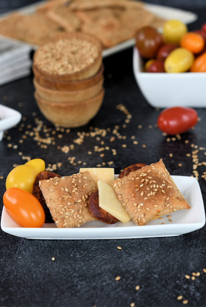 a plate with sourdough whole wheat crackers, cheese, sausage and tomatoes