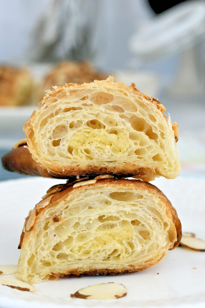a slice almond croissant showing the layers and filling