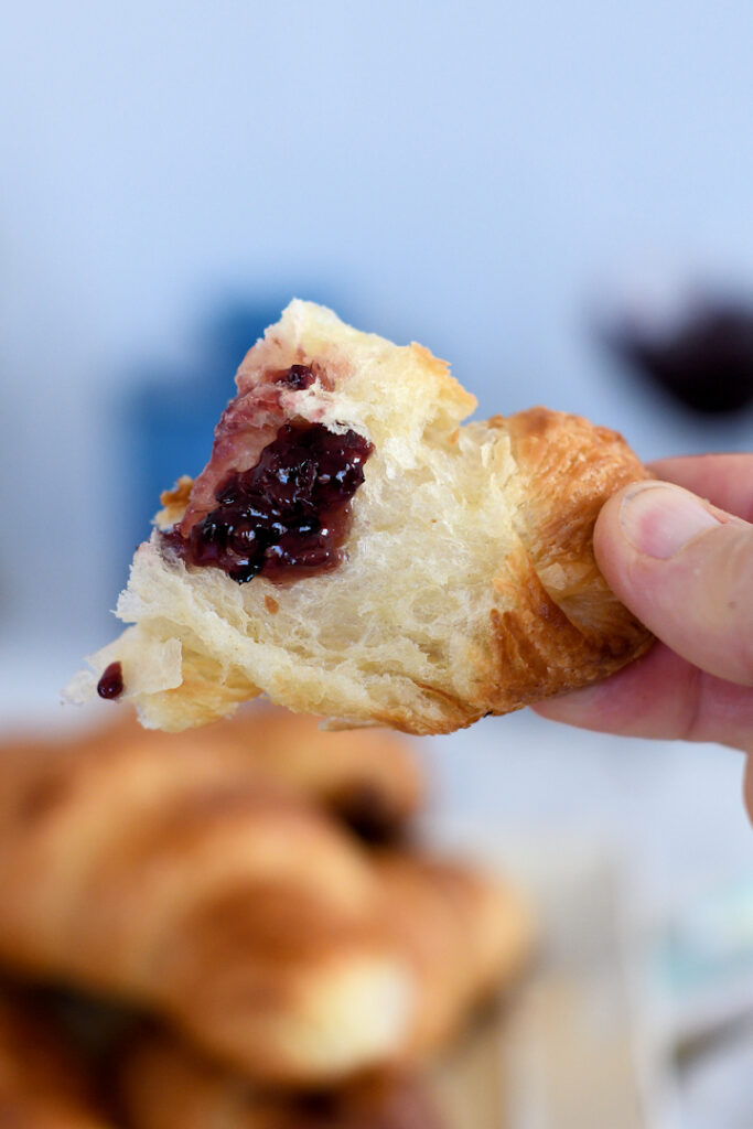 a hand holding a piece of croissant topped with fruit preserves