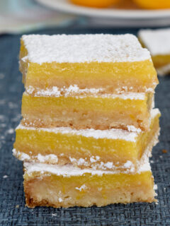 a stack of meyer lemon bars on a blue surface