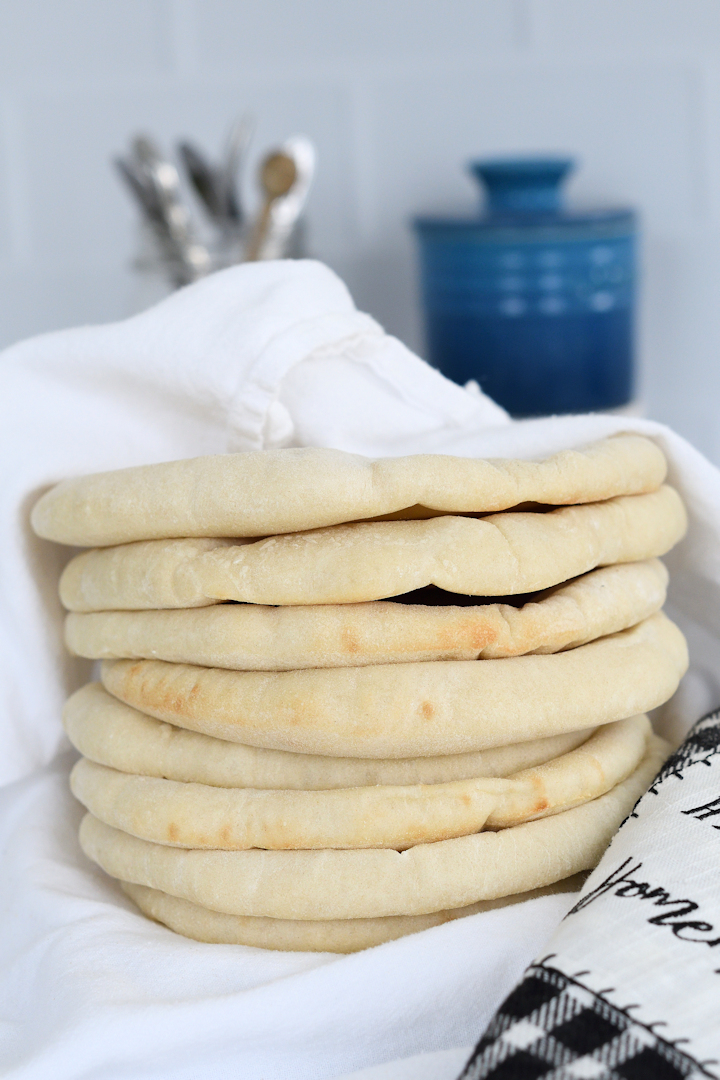 a stack of homemade pita bread wrapped in a towel