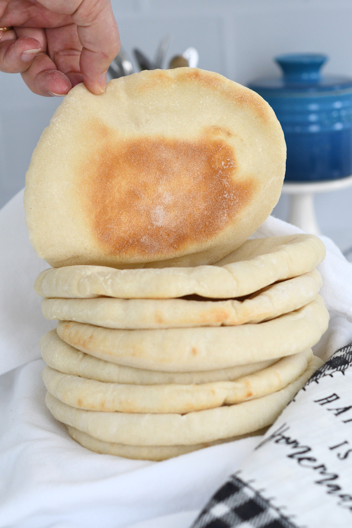 a stack of pita breads, with one showing the golden brown bottom side